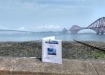 TW Reisgids op muurtje voor Firth of Forth Bridge klein